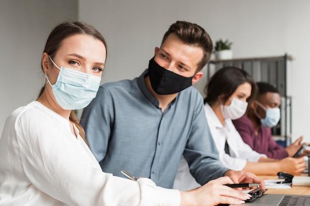 Ludzie W Biurze Pracujący Razem W Czasie Pandemii W Maskach Darmowe Zdjęcia