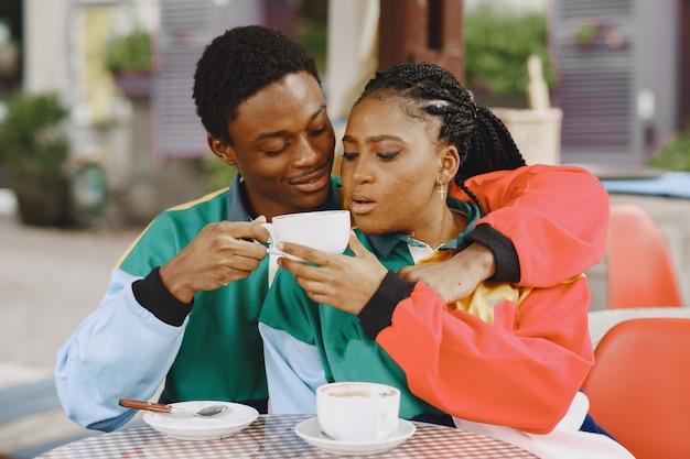 Ludzie W Identycznych Ubraniach. Afrykańska Para W Mieście Jesienią. Ludzie Przy Stole. Darmowe Zdjęcia