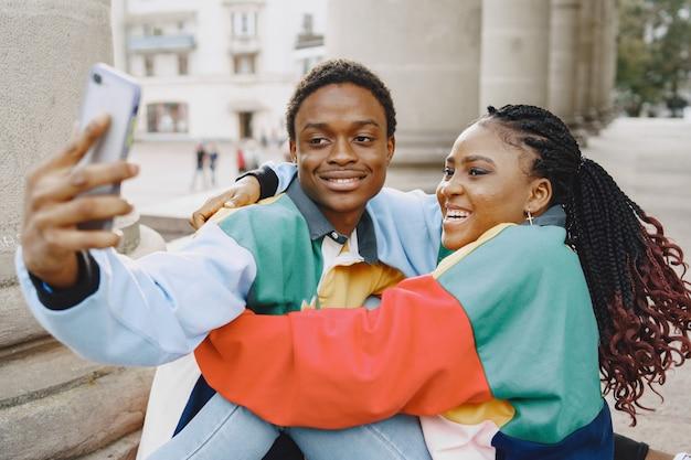 Ludzie W Identycznych Ubraniach. Afrykańska Para W Mieście Jesienią. Ludzie Siedzący I Używający Telefonu. Darmowe Zdjęcia