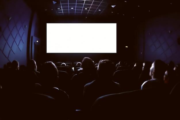 Ludzie W Kinie Oglądają Film. Pusty Pusty Biały Ekran Premium Zdjęcia