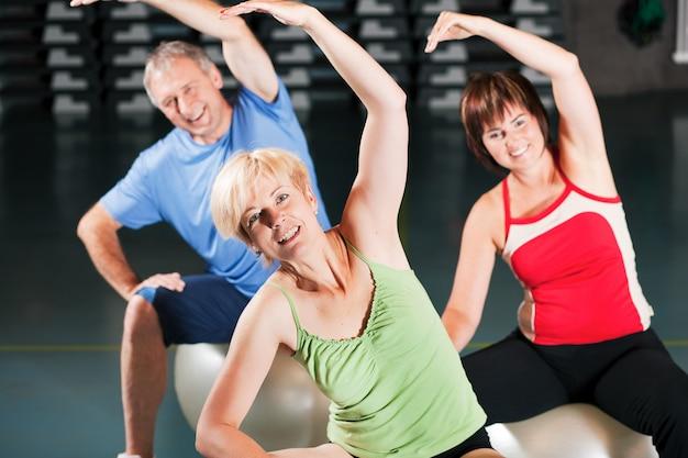 Ludzie w siłowni na piłkę do ćwiczeń Premium Zdjęcia