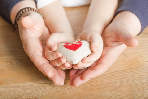 Ludzie, Wiek, Rodzina, Miłość I Opieki Zdrowotnej Pojęcie, - Zamyka Up Starsza Kobieta I Chłopiec Wręcza Mieniu Czerwonego Serce Nad Drewnianym Tłem Premium Zdjęcia
