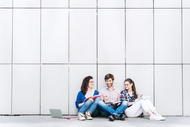 Ludzie Z Książek I Gadżetów Siedząc Na Podłodze W Pobliżu ściany. Edukacja Koncepcji Social Media. Premium Zdjęcia