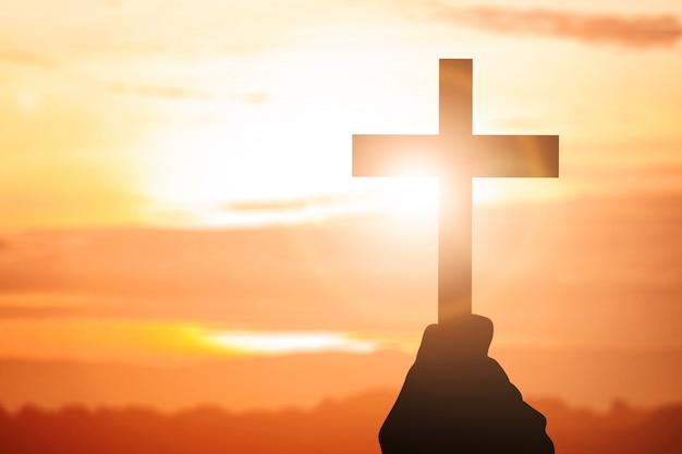 Ludzką ręką trzyma krzyż chrześcijański Premium Zdjęcia