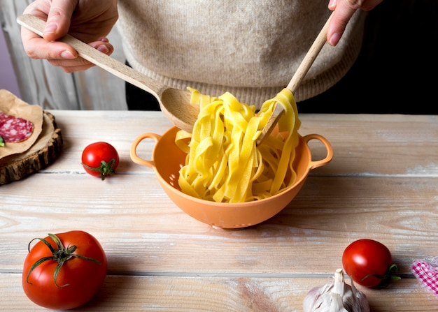 Ludzkie ręce z drewnianymi łyżkami, mieszając gotowane spaghetti w durszlak na blacie kuchennym Darmowe Zdjęcia