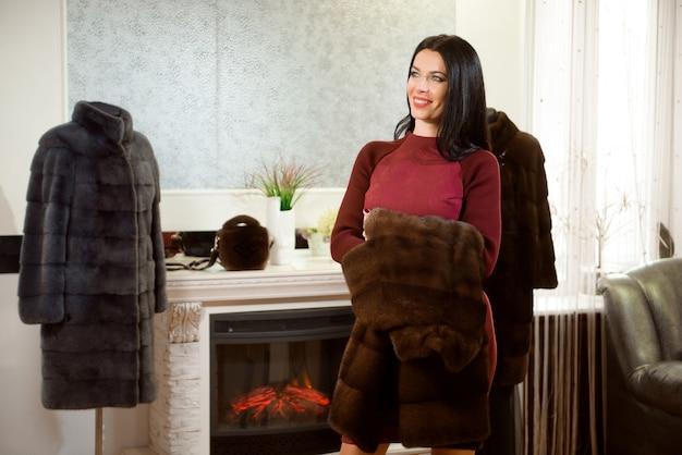 Luksusowa Koncepcja Odzieży. Kobieta Z Futrem. Dziewczyna W Płaszcz Futra W Sklepie Z Futra Na Tle. Premium Zdjęcia