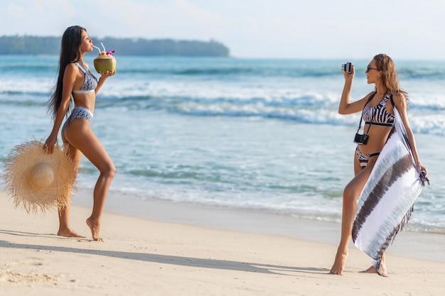 Luksusowe brunetki to wykrzywiona plaża. azjatka pije koktajl kokosowy, a europejczyk strzela do niej kamerą retro. Premium Zdjęcia