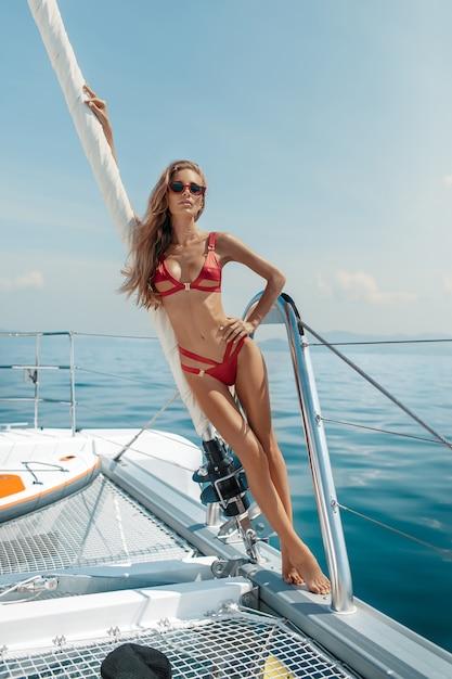 Luksusowe wakacje: piękna blondynka w otwartym morzu na jachcie w seksownym czerwonym bikini i czerwonych okularach przeciwsłonecznych. czas letni wakacje na tropikalnych wyspach. Premium Zdjęcia
