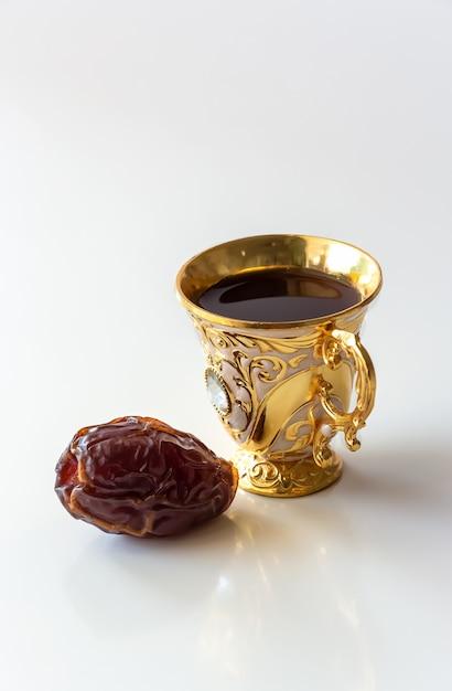 Luksusowy Arabski Złoty Kubek Czarnej Kawy I Daty Białe Tło. Koncepcja Ramadanu. Premium Zdjęcia