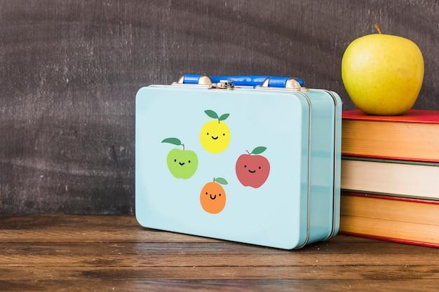 Lunchbox w pobliżu stosu książek i jabłka Darmowe Zdjęcia