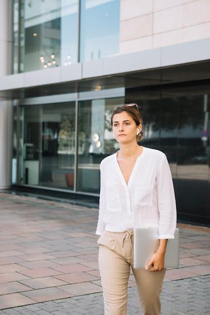 Młody bizneswomanu odprowadzenie przed korporacyjnym budynkiem Darmowe Zdjęcia