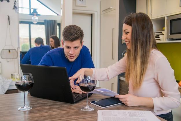 M? oda para szuka dokumentów finansowych w laptopie przy stole w domu wn? trza. młodzi studenci domowi oferujący usługi e-learningowe Premium Zdjęcia