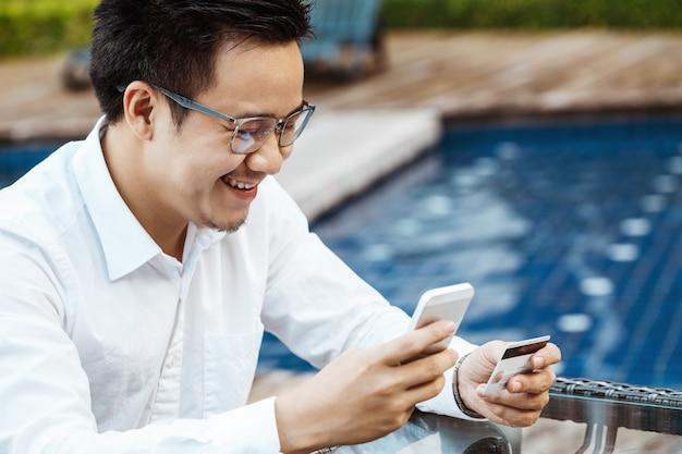 M? Ody Przystojny M ?? Czyzna Lubi Zakupy Online Przez Telefon Komórkowy Z Karty Kredytowej. Darmowe Zdjęcia
