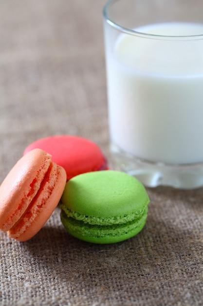 Macaron Trzy Kawałki Czerwony, Zielony, Pomarańczowy I Szklanka Z Mlekiem Na Płótnie Obrus. Premium Zdjęcia