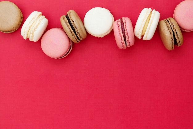 Macarons Ciasta Lub Ciasteczka Na Czerwonym Tle. Leżał Płasko. Skopiuj Miejsce Premium Zdjęcia