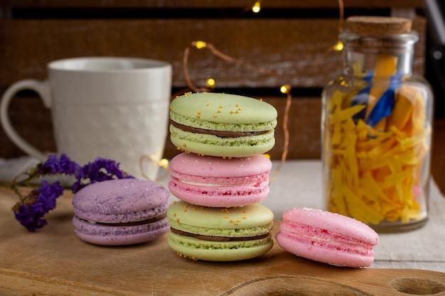 Macarons I Filiżanka Kawy Na Drewnianym Stole Premium Zdjęcia