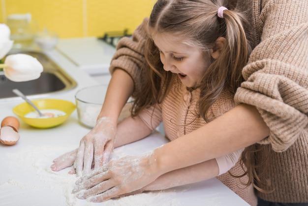 Macierzysta i szczęśliwa córki kładzenia mąka na stole Darmowe Zdjęcia