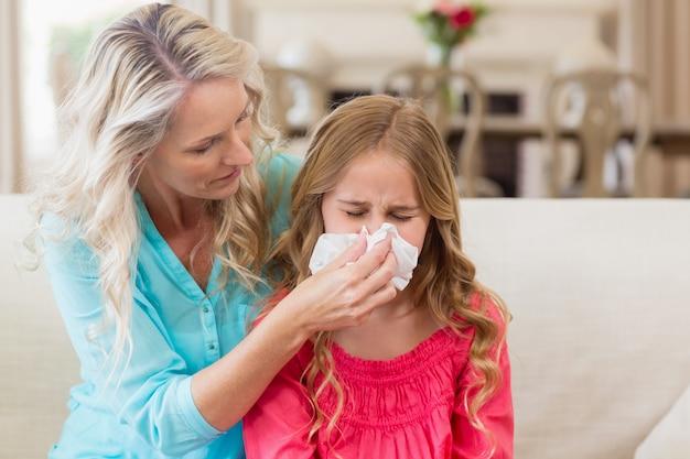 Macierzysta Pomaga Córka Dmucha Jej Nos Na Kanapie Premium Zdjęcia