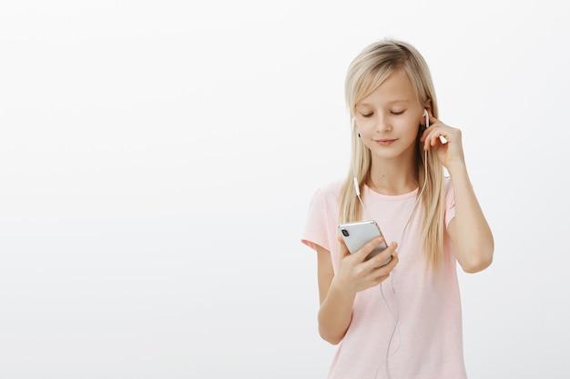 Mądra Dziewczyna Wie Wszystko O Gadżetach. Portret Słodkie Piękne Blond Młode Dziecko, Noszenie Słuchawek I Zbieranie Piosenki W Smartfonie Darmowe Zdjęcia