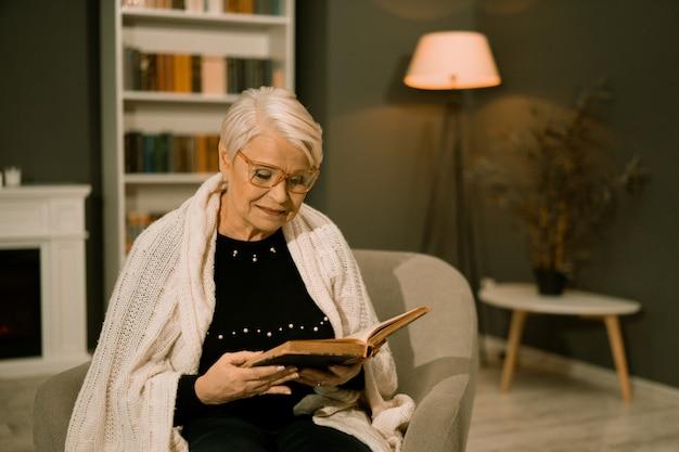 Mądra Starsza Kobieta Czyta Starą Książkę W Okularach Premium Zdjęcia