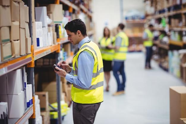 Magazynowy pracownik używa ręka skaner w magazynie Premium Zdjęcia