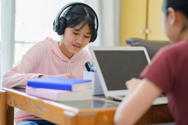 Mając Lekcję Online. Azjatyckie Dzieci Samodzielnie Uczą Się Z E-learningiem W Domu. Koncepcja Edukacji Online I Samokształcenia Oraz Nauczania W Domu. Premium Zdjęcia