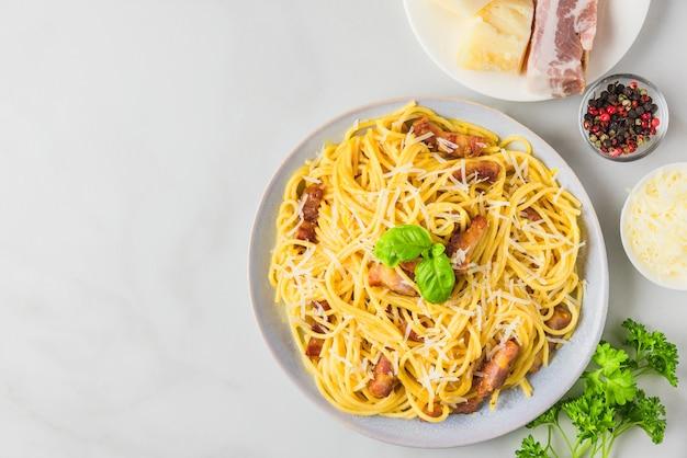 Makaron Carbonara, Spaghetti Z Bekonem, Jajkiem, Twardym Parmezanem I Bazylią W Talerzu. Tradycyjna Kuchnia Włoska Premium Zdjęcia