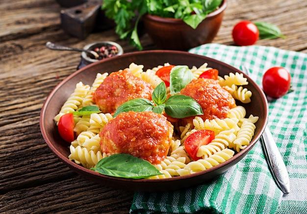 Makaron fusilli z klopsikami w sosie pomidorowym i bazylią w misce, kuchnia włoska. Premium Zdjęcia