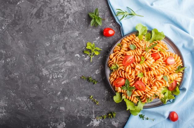 Makaron fusilli z sosem pomidorowym, pomidorami cherry, sałatą i ziołami Premium Zdjęcia