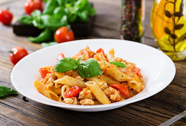Makaron Penne W Sosie Pomidorowym Z Kurczakiem, Pomidorami, Ozdobiony Bazylią Na Drewnianym Stole. Włoskie Jedzenie. Makaron Bolognese. Premium Zdjęcia