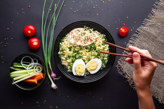 Makaron Ramen Miska Z Kurczakiem, Warzywami I Jajkiem Na Czarnym Tle Widok Z Góry. Premium Zdjęcia