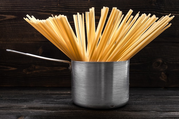 Makaron spaghetti w retro aluminiowej patelni z uchwytem na ciemnym drewnianym biurku Premium Zdjęcia
