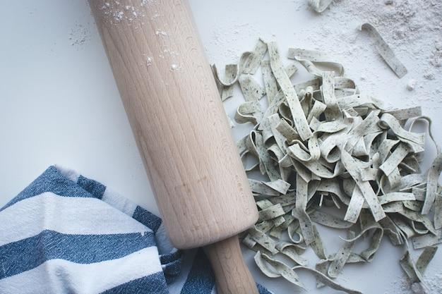 Makaron tagliatelle objęte mąki z drewnianym wałkiem na białym tle Darmowe Zdjęcia