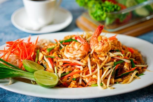 Makaron Tajskie Jedzenie, Pad Tajski Na Niebieskim Tle Z Cebulą I Limonką Obok Płyty Premium Zdjęcia