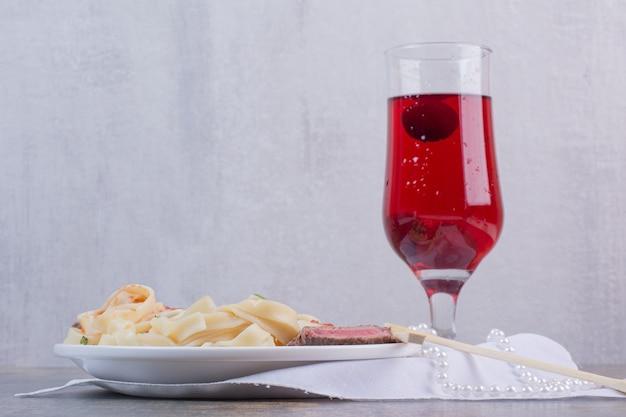 Makaron Z Mięsem I Szklanką Czerwonej Lemoniady Na Białym Talerzu Darmowe Zdjęcia