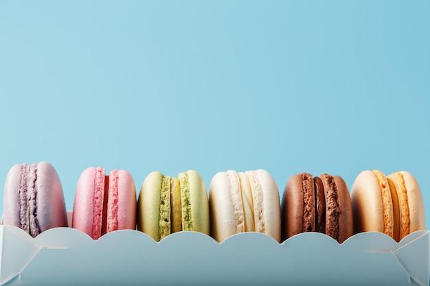 Makaronowi Ciastka Różni Kolory W Białym Pudełku Na Błękitnym Tle. Premium Zdjęcia