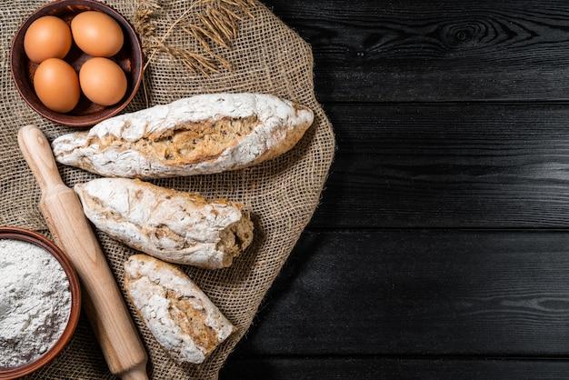 Mąkę W Drewnianej Misce Na Ciemnym Drewnianym Stole Z Kłoskami Pszenicy, Jajek, Mleka I Masła, Widok Z Góry Z Miejsca Kopiowania. Premium Zdjęcia