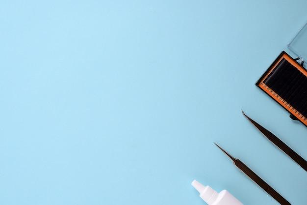 Makeup Muśnięcia I Kosmetyki Na Błękitnym Tle. Widok Z Góry, Płaski Układ, Przestrzeń Do Kopiowania Premium Zdjęcia