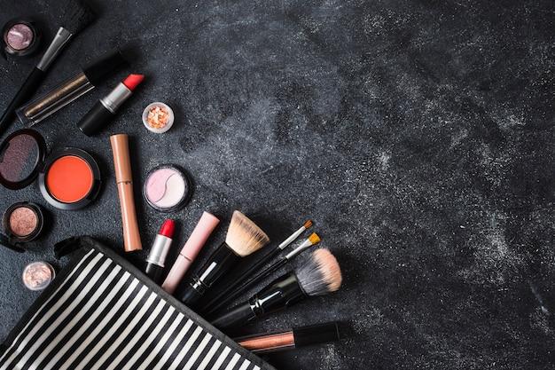 Makeup produkty i pasiasta kosmetyczna torba na zakurzonym ciemnym tle Darmowe Zdjęcia