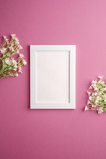 Makieta Białej Pustej Ramki Na Zdjęcia Z Kwiatami Chwastów Myszowatych Na Różowym Fioletowym Tle, Miejsce Na Kopię Widoku Z Góry Premium Zdjęcia