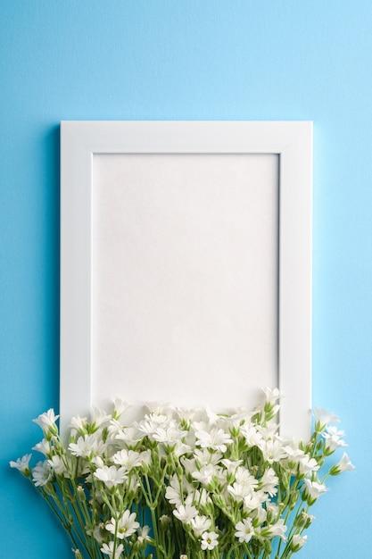 Makieta Białej Pustej Ramki Na Zdjęcia Z Kwiatami Ciecierzycy Na Niebieskim Tle, Widok Z Góry Na Kopię Premium Zdjęcia