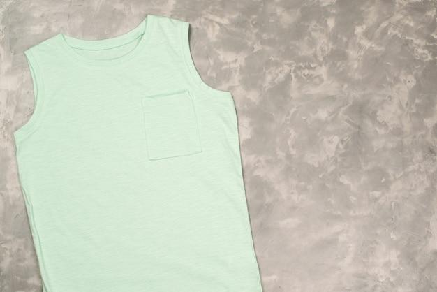 Makieta Kolorowej Koszulki, Widok Z Góry. T-shirt Na Betonowym Szarym Stole, Miejsce Na Kopię. Premium Zdjęcia