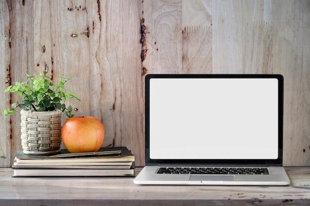Makieta laptop z książką, jabłkiem i houseplant na drewnianym stole. Premium Zdjęcia