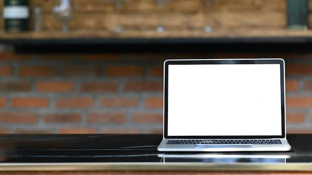 Makieta Laptopa Z Białym Pustym Ekranem Stawiającym Na Zewnątrz Na Nowoczesnym Stole Z Klasycznym Barem Kuchennym As Premium Zdjęcia