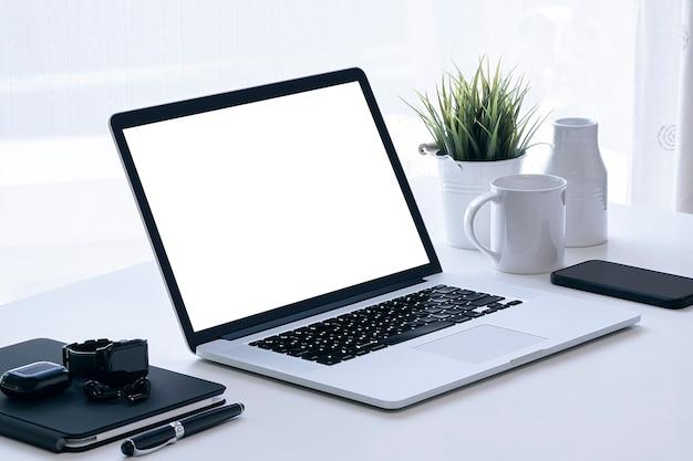 Makieta Laptopa Z Ekranem Balnk I Gadżet Na Białym Stole Z Jasnym Jasnym Tłem. Premium Zdjęcia