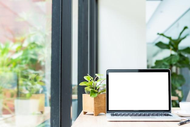 Makieta laptopa z pustym ekranem z filiżanką kawy na stole w kawiarni Premium Zdjęcia