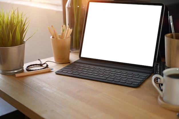Makieta nowoczesna tabletka z klawiaturą na drewnianej przestrzeni roboczej i przestrzeni kopii. Premium Zdjęcia