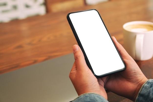 Makieta Obrazu Rąk Trzymających Czarny Telefon Komórkowy Z Pustym Ekranem Pulpitu Z Laptopem I Filiżanką Kawy Na Stole Premium Zdjęcia