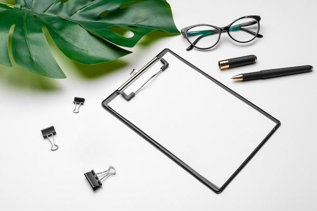 Makieta obszaru roboczego biura domowego ze schowkiem, liściem palmowym i akcesoriami. Premium Zdjęcia