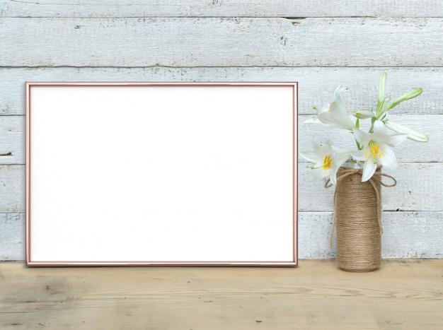 Makieta Poziomej Ramki A4 W Kolorze Różowego Złota Z Bukietem Lilii Stoi Na Drewnianym Stole Premium Zdjęcia